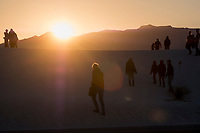 People watch the sunset at White Sands National Monument near Alamogordo, New Mexico, USA, on Fri., Dec. 29, 2017.
