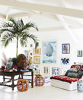 The living room is decorated with vintage posters and watercolours and a collection of colourful textiles