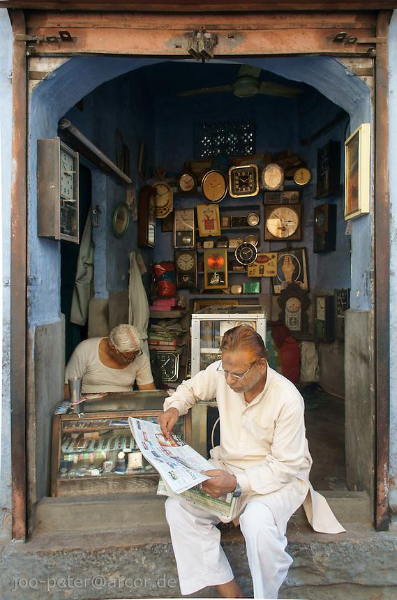 man reading newspaper  in front of shop for clocks in Jodhpur, Rajastan, India