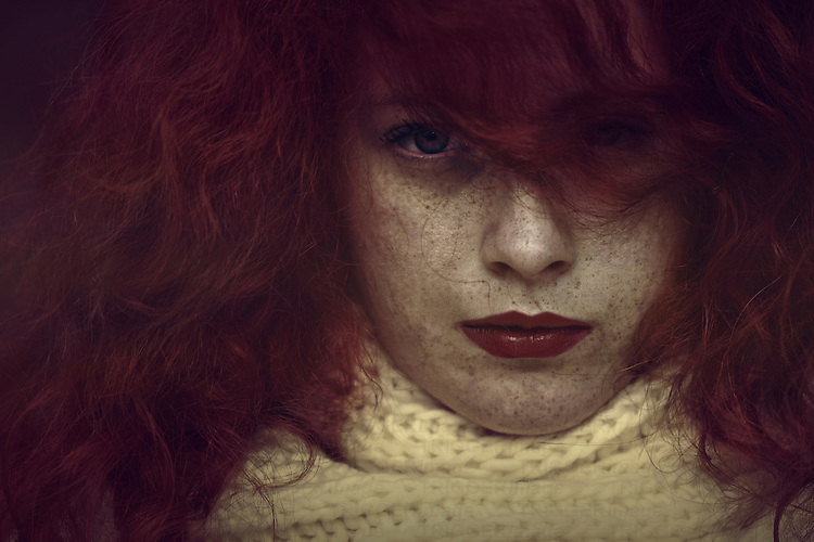 Close-up portrait of a young female with freckles, red curly hair and piercing green eyes looking at camera