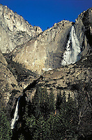 Heavy flow of water over Yosemite Falls. Ice apron flanks upper cascade. Lower cascade pours into shadowy basin. Crisp blue sky. California USA Yosemite Valley.