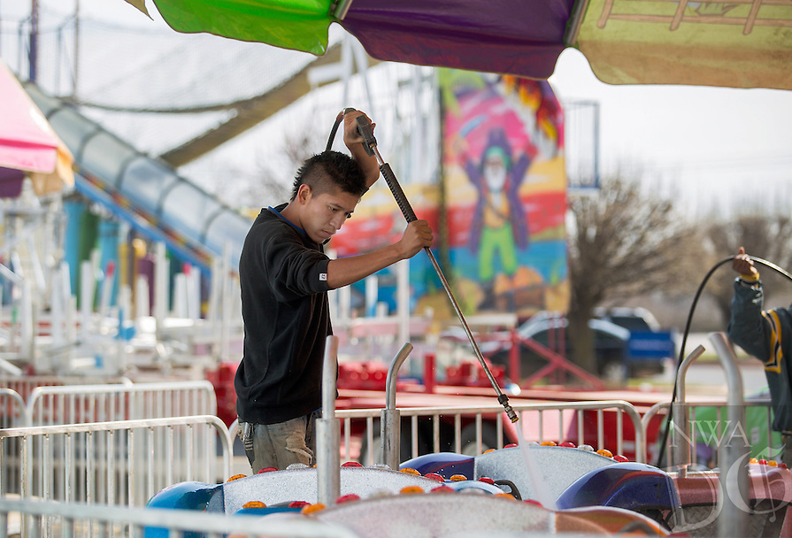 NWA Democrat-Gazette/JASON IVESTER --03/17/2015--<br /> Jose Garcia with Pride Amusements washes one of the rides on Tuesday, March 17, 2015, in the parking lot of the Frisco Station Mall in Rogers. The Pride Amusements Spring Time Carnival opens today (WEDNESDAY) and continues through March 28.