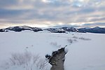 Idaho, south central, Custer County, Stanley. A meandering stream through a snow covered valley looking towards the White Cloud Mountains in winter.