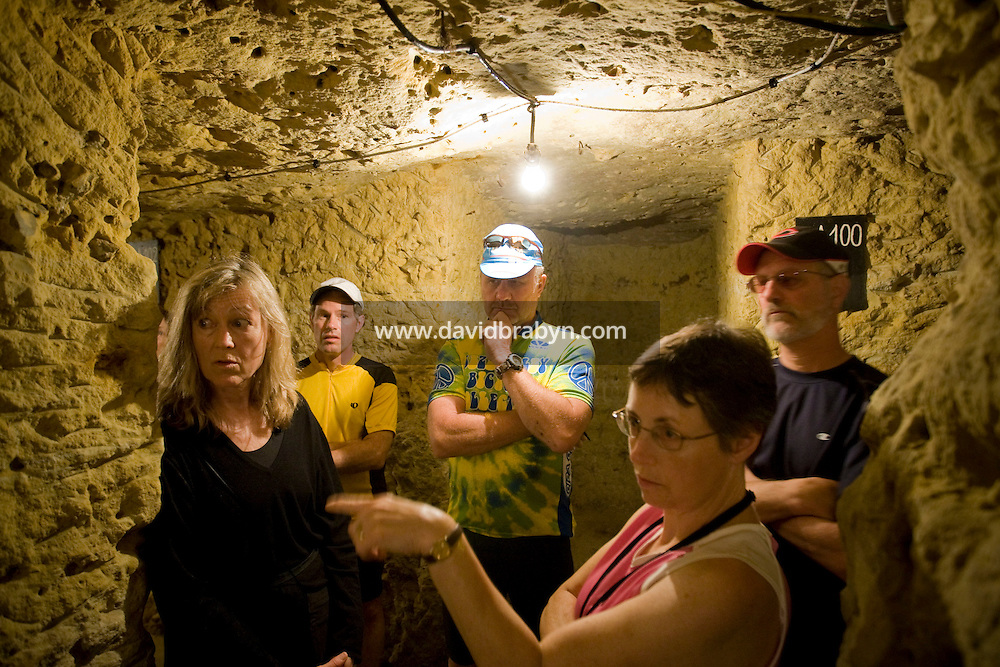 Participants in a Backroads cycle tour of the Loire Valley listen to winemaker Daniel Jarry (not seen) explanations in his cellars in Vouvray, France, 26 June 2008.
