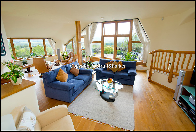 BNPS.co.uk (01202 558833)<br /> Pic: Strutt&amp;Parker/BNPS<br /> <br /> ***Please use full byline***<br /> <br /> The lounge.<br /> <br /> A stunning country pad that looks like it could have been designed by Hobbit hero Bilbo Baggins has gone on the market for one million pounds.<br /> <br /> The wonderfully wacky house appears to blend in with its surroundings, just like the Lord of the Rings character's humble Hobbit hole.<br /> <br /> The plush five-bedroom property is nestled deep in the rolling hills of Wales' Snowdonia National Park - although it would not look out of place in Middle Earth.<br /> <br /> The house is called Cynefin, meaning 'a sense of place' in Welsh, and is in the tiny village of Llanegryn in Gwynedd wih unrivalled views over the Dysynni Valley.<br /> <br /> It is on the market through estate agents Strutt and Parker for &pound;985,000.