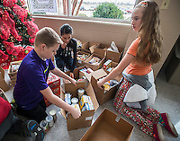 STAFF PHOTO ANTHONY REYES &bull; @NWATONYR<br /> Alex Bowers, 13, from left, Kassandra Garcia, 12, and Alexis Samarin, 13, all students at Tyson Middle School organize boxes of donated food Tuesday, Dec. 16, 2014 at the school in Springdale. The school collected non-perishable food items to be given to local agencies and families at the school in need.