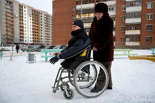 Russian army hazing victim Andrei Sychyov uses a wheelchair outside his home in Yekaterinburg, pushed by his mother, Galina Sychyova. .On New Yearís Day in 2006 in the barracks of the Chelyabinsk Tank Academy, a sergeant, possibly drunk, meted out punishment to Pvt. Andrei S. Sychyov..Private Sychyov was forced to squat for three and a half hours. When he complained, as the pain worsened, the sergeant stomped on his ankle twice..Private Sychyov suffered injuries that resulted in infection, then in the amputation of his both legs, a finger, and genitals. .His case became the biggest scandal to reflect the state of Russia's army and the country's human rights situation.
