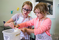 "Sienna Lasater, 12, (from left) and Cassidy Lasater measure powdered sugar, Monday, July 27, 2020 during cooking camp for kids at Young Chefs Academy in Bentonville. The academy is hosting a four day cooking camp. The kids gain some culinary experience baking and cooking. They made a casserole, rocky road cookies, Mardi Gras cupcakes, fruit pops and cream cheese frosting. No prior experience is required and kids of all skill levels can participate in the camp. ""Charles, he said he was six. His favorite dish is quiche lorraine,"" said head chef Mary Nieto, praising his culinary knowledge. Check out nwaonline.com/200728Daily/ for today's photo gallery. <br /> (NWA Democrat-Gazette/Charlie Kaijo)"