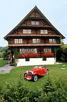 Switzerland.  Canton Zoug. Steinhausen. 350 years old house. Wooden chalet. A red antique convertible sport car is parked in the garden.  © 1989 Didier Ruef