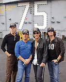 "Norfolk, Va., aboard USS Harry S. Truman (CVN 75) - October 9, 2002 -- Internationally renowned rock band ""Aerosmith"" (from left:  Tom Hamilton, Joey Kramer, Joe Perry, and Steven Tyler) visited with Truman Sailors and toured the aircraft carrier pier side at Norfolk Naval Station.  The band had returned to perform in the area, having cancelled their original performance scheduled for September 11, 2001.  .Credit: Christopher B. Stoltz - U.S. Navy via CNP."