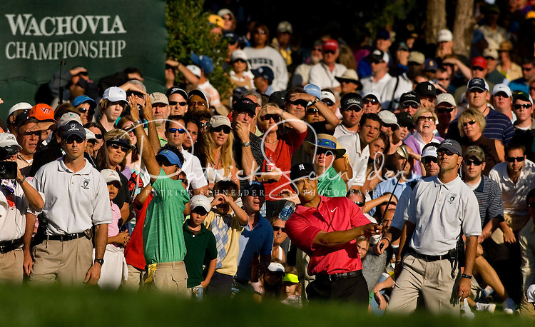 TIger Woods hits the ball from the rough with a large crowd of spectators looking on during the 2007 Wachovia Championships at Quail Hollow Country Club in Charlotte, NC.