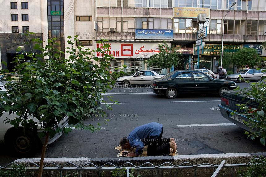 Un uomo prega in una strada di Teheran. Normal life in Tehran.