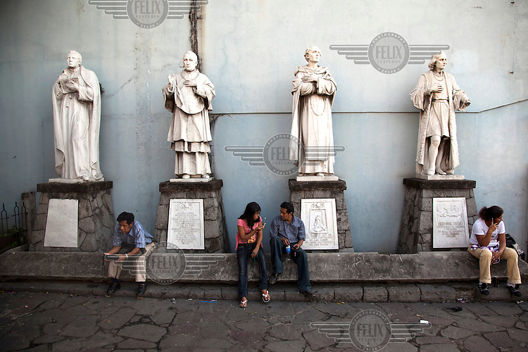 People sit beneath four statues. From left to right: Jose Miguel Funes, Don Jorge Viteri, a former Bishop of San Salvador in the 19th century, Frey Bartolome de Las Casas, a 15th Century Spanish priest, Bishop and author, and Cristobal Colon (Christopher Colombus).
