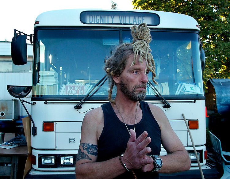 PDX3-DIGNITY VILLIAGE--(9/25/03)-.Jack Tafari is president of the residents governing council. He is standing in front of the bus that is permanently parked at Diginity Village. The bus houses the village library and has a the only working television on the site.  Dignity Villiage is a collection of homeless people who live together in a village on the outskirts of Portland, Oregon.  (Photo By Alan S. Weiner .)