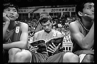 A player of Dongguan Guangming Middle School reads a Chinese basketball magazine before the start of the final match of a nationwide 3-a-side basketball tournament in Guangzhou, November 2011.