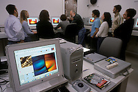 College professor and students gathered around computers in Photography class.