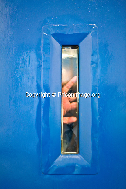 A prison officer makes a visual assessment of a cell before entering it during a training exercise. HMP Wandsworth, London, United Kingdom
