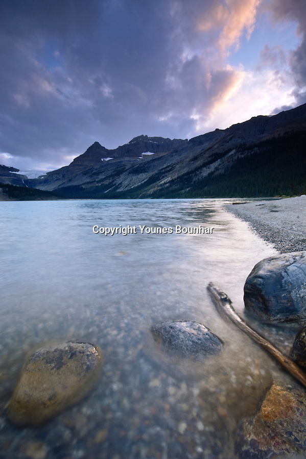 Storm clearing at Bow Lake, with rocks in the foreground and tumultuous waters