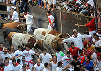 Participants run ahead of Alcurrucen fighting bulls during the San Fermin Festival´s running of the bulls, on July 7, 2013, in Pamplona, Basque Country. On each day of the eight San Fermin festival days six bulls are released at 8:00 a.m. (0600 GMT) to run from their corral through the narrow, cobbled streets of the old navarre town over an 850-meter (yard) course. Ahead of them are the runners, who try to stay close to the bulls without falling over or being gored. (Ander Gillenea / Bostok Photo)