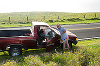 A cute older couple with a red truck pause along Saddle Road, Big Island.