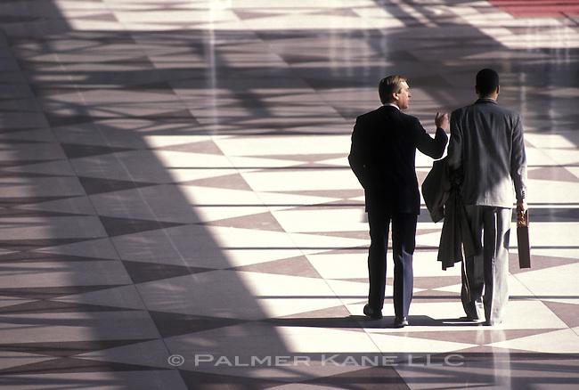 Businessmen walking in corporate atrium