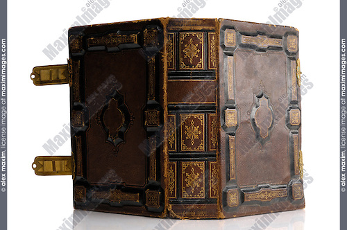 Closeup of rustic ancient book with hard ornamental leather cover and shiny brass clasps Isolated silhouette on white background
