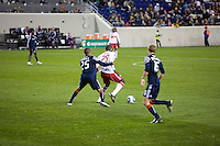 New England's Darrius Barnes and New York's Salou Ibrahim fight for the ball as the New York Red Bulls play their final match of the season against the New England Revolution at Red Bull Arena in Harrison, New Jersey on 21 October 2010.