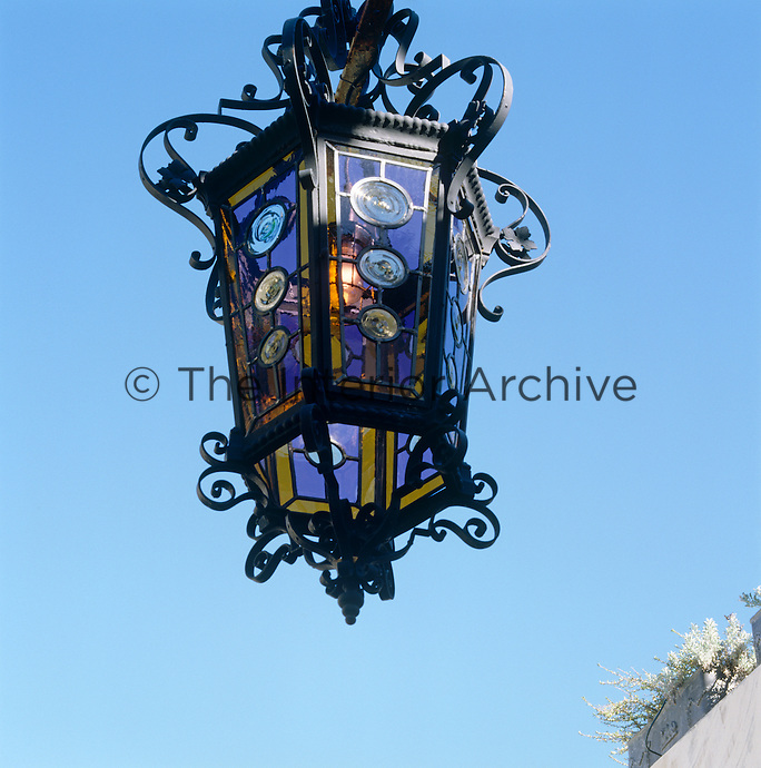 Seen against the bright blue Cape Town sky an ornate garden lantern constructed from wrought-iron and stained glass