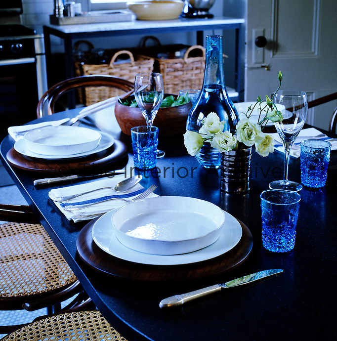 The slate-topped kitchen table is laid with white crockery and blue glassware