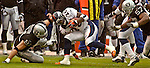 Oakland Raiders defensive end Tyler Brayton (91) stops Denver Broncos running back Clinton Portis (26) on Sunday, November 30, 2003, in Oakland, California. The Broncos defeated the Raiders 22-8.