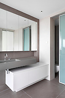 A modern bathroom with a mirrored cupboard set in a recess above a wall mounted washbasin. A set of cupboards beneath the sink provides storage.