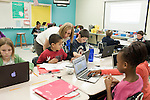 November 15, 2011. Mooresville, NC.. Elena DaCosta, center, a math teacher at East Mooresville Intermediate School, helps a 4th grader with his math lessons. Much of the class work consists of computer based math tutorials which are turned in electronically.. The Mooresville school system has become nationally known for being on the cutting edge of using technology as an educational tool. Starting in 3rd grade, each student is issued their own laptop that they will use in class and at home to further their learning.