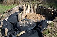 Anlage eines Sanddariums im Garten, Schritt 3: als Umrandung werden Eichenspaltpfähle, Eichenspaltpfahl, Holzpfähle in den Graben gestellt und mit Sand befestigt. Sandarium, Sand, Sandfläche, Sandhaufen im Garten, Naturgarten, Nisthilfe für Wildbienen und solitäre Wespen, Lebensraum für Eidechsen, Eidechse. Soll verschiedenen Insekten als Unterschlupf, Nistplatz, und Nahrungsquelle dienen. Mehr als die Hälfte der Wildbienenarten, welche Nester bauen, nisten im Erdboden. Wildbienen-Nisthilfen, Wildbienen-Nisthilfe selbermachen, selber machen, Wildbienenhotel, Insektenhotel, Wildbienen-Hotel, Insekten-Hotel