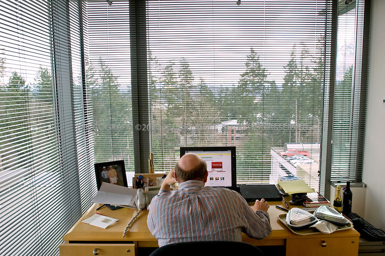 1/23/2007--Redmond, WA, USA..12:17pm: Steve Ballmer, CEO of Microsoft, takes a quick  lunch break at his desk while checking his email. When in the Microsoft office, Ballmer will usually eat food from Microsoft's cafeteria, sitting at his desk catching up on correspondence. Ballmer's small, simple desk is nestled in the corner of a small, low key office on the 5th floor of a building on the Microsoft campus with views of Washington State's Cascade mountains to the east...Photograph ©2007 Stuart Isett.All rights reserved