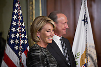 Betsy DeVos, United States Secretary of Education, stands with her husband Dick DeVos Jr., right, before being sworn in by U.S. Vice President Mike Pence in the Vice President's Ceremonial Office in Washington, D.C., U.S., on Tuesday, Feb. 7, 2017. DeVos squeaked through a history-making Senate confirmation vote to become U.S. education secretary, as Vice President Mike Pence broke a 50-50 tie and Republicans staved off last-minute defections that would have killed her nomination. Photo Credit: Andrew Harrer/CNP/AdMedia