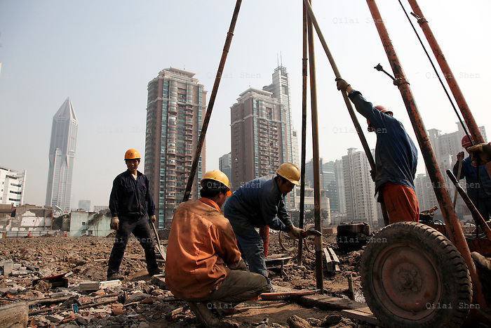 Workers drill holes at a demolished old neighborhood slated for new residential construction in Shanghai, China on 11 February, 2009.   Workers operate a drill on an empty lot, once an old residential neighborhood, in Shanghai, China on 11 February, 2009.  Large swaths of land in Shanghai has been cleared for new development in recent years, moving former residents out of the center of the city and driving up real estate prices in the process.  For the past decade, Shanghai has underwent the largest reconstruction in recorded history, over 20 million square meters of land, approximately a third of Manhattan, were developed between year 200 and 2005 alone.