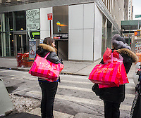 Tourists with their Victoria's Secret purchases in Midtown Manhattan in New York on Sunday, January 26, 2014 (© Richard B. Levine)