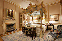 An opulent bedroom with a four poster bed with an ornate gilt top. The room is decorated in pale blue and cream tones.