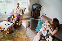 Fred Bermont and daughter Elyse Bermont (age 2.5) (at left) watch Sesame Street while wife Jen Bermont and son Dylan Bermont (age 9 months) sit in their home Lexington, Massachusetts, USA, before he goes to work and drops the kids off at day-care on June 9, 2014. Bermont is the father of two children and shares parenting duties with his wife, Jen Bermont. Fred usually takes care of the morning routine, including feeding, dressing, and dropping the kids off at day-care, and Jen picks them up and watches over them in the afternoon. Fred is a Senior Clinical Standards Specialist at Shire, a pharmaceutical company with headquarters in Lexington.