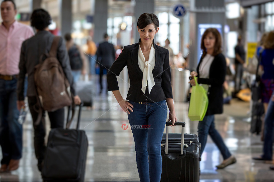 Businesswoman traveling with luggage suitcase in hand at the Austin–Bergstrom International Airport (ABIA) Terminal in Austin, Texas.