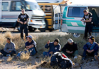 2/16/07 Members of the state's Gang & Immigration Intelligence Team Enforcement Mission (G.II.T.E.M) stand near a van full of undocumented immigrants that that stoped along I-10 Friday.  (Pat Shannahan/ The Arizona Republic)