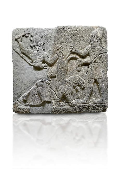 Picture & image of Hittite relief sculpted orthostat stone panel of Herald's Wall Basalt, Karkamıs, (Kargamıs), Carchemish (Karkemish), 900-700 B.C. Anatolian Civilisations Museum, Ankara, Turkey.<br /> <br /> On the right is a bearded human figure with a short skirt; with the dagger in his right hand, he is stabbing the lion standing on his front legs while holding the lion's tail with his left hand. On the left is a bearded god figure with a horned-headdress, who grasps the lion's hind leg while holding the ax over his head with his right hand. <br /> <br /> Against a white background.