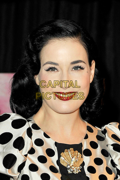 DITA VON TEESE.Dita Von Teese attends a photocall at Erotica 2010, the world's largest lifestyle show for adults, at Olympia Exhibition Centre, London, England..November 19th, 2010.headshot portrait black white polka dot  silk satin brooch gold red lipstick make-up beauty .CAP/MAR.© Martin Harris/Capital Pictures.