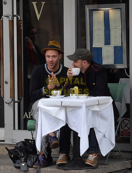 WILL YOUNG & FRIEND.Enjoying a coffee on Great Portland Street, London, England, UK, .October 30th 2009..full length sitting table cafe outside drink grey gray jumper top cap hat hands together  sweater .CAP/IA.©Ian Allis/Capital Pictures