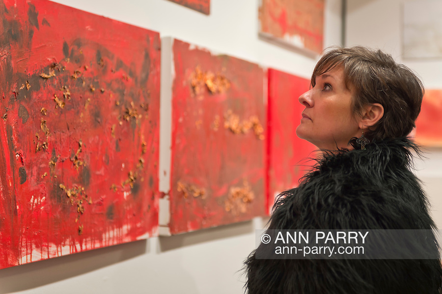 Huntington, New York, U.S. - March 1, 2014 - A visitor looks at the exhibit 'Red & White Paintings & Photographs – El Vocio Existential,' by artist Barry Feuerstein at the Opening Reception '3 Wild & Crazy Artists' at FotoFoto Gallery.