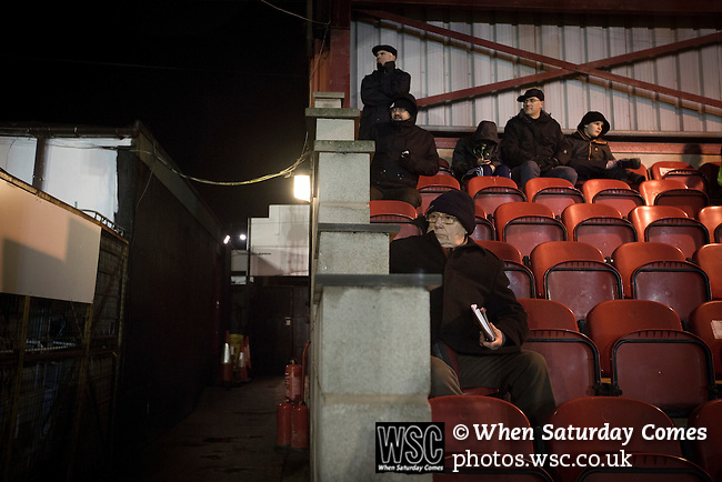Ashton United 6 Ramsbottom United 0, 12/01/2016. Hurst Cross stadium, Northern Premier League. Spectators in the main stand watching the second-half action during the fixture between Ashton United and Ramsbottom United in the Northern Premier League premier division. The match was played at Ashton's Hurst Cross stadium, the club's ground. The club was originally founded in 1878 as Hurst F.C. and by 1880 the club were playing at Hurst Cross, their current ground which makes their home one of the oldest football grounds in the world. Ashton won the match 6-0, watched by a crowd of 178. Photo by Colin McPherson.