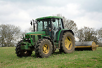 Tractor driven by female farm worker rolling field for hay production in spring in Southern England
