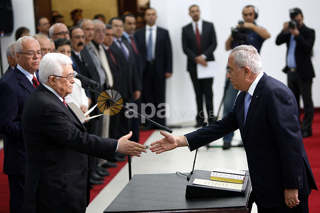 (FILES) This file photo taken on May 16, 2012 shows Palestinian President Mahmoud Abbas and his Prime Minister Salam Fayyad, receive the new government Ministers during the swearing in ceremony of the new cabinet, at Abbas's headquarters in the West Bank town of Ramallah. According to media, a sudden meeting was held between Palestinian President Mahmoud Abbas and former Palestinian Prime Minister Salam Fayyad, before days ago, in the West Bank city of Ramallah. Photo by Issam Rimawi
