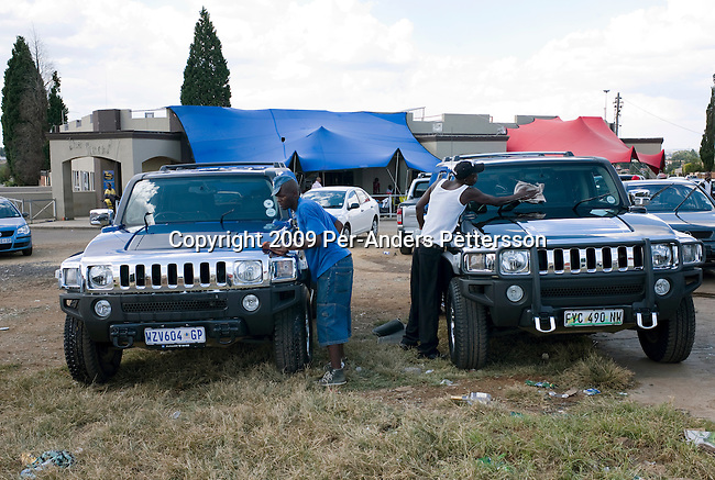 SOWETO, SOUTH AFRICA MARCH 8: Attendants wash Hummer cars at an outside car wash on March 8, 2009 in Soweto, South Africa. Many of the recent educated and affluent black people that have grown up in the poor townships are now living a middle-class or affluent life in the former white suburbs. Many come back on the weekends to visit family and friends. (Photo by: Per-Anders Pettersson/Getty Images)...