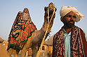 Rajasthani dancers in traditional costumes sitting on camel in desert camp; Rajasthan, India --- Model Released